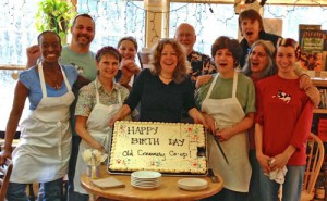"Old Creamery staff and selling owners Alice and Amy celebrate the Co-op's purchase of the Creamery with a ""Happy Birth Day"" cake. Credit: Old Creamery Co-op"