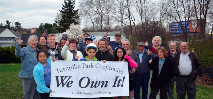 "Turnpike Park Cooperative residents hold a banner saying ""We Own It!"""