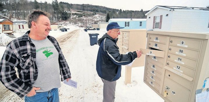 Two men check a community mailbox in the Weston's Mobile Home Park, smiling and chatting with one another
