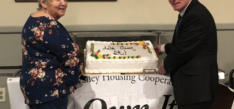 "Two Sherwood Village residents pose with a cake saying ""We Own It!"" in frosting"