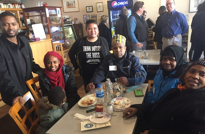 Five members of Isuken Co-op, a Somali-Bantu cooperative, join Mo Manklang of the US Federation of Worker Cooperatives at a table with snacks
