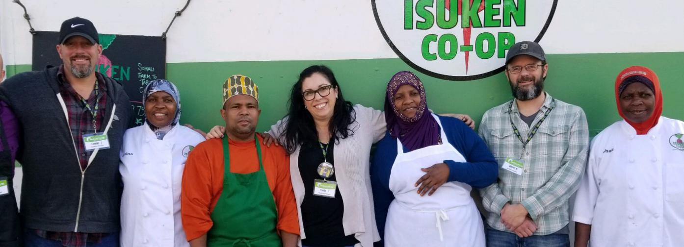 Members of Isuken Co-op and Belfast food co-op pose in front of Isuken's food truck